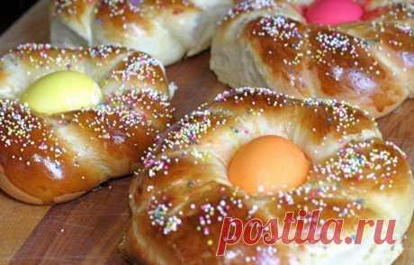 Пасхальные гнёзда  Эти несладкие сдобные булочки, сплетённые в виде гнёзд, олицетворяют домашний уют и прекрасно подходят к пасхальному столу. Приготовить их сможет даже начинающий кулинар.  Ингредиенты:  • 500 г муки; • 300 мл молока; • 100 г сливочного масла; • 2 куриных яйца; • 2 ст. л. сахара; • 1,5 ч. л. соли; • 2,5 ч. л. сухих дрожжей; • окрашенные куриные яйца; • декоративная пасхальная посыпка.  Приготовление  Соедините дрожжи, тёплое молоко и половину муки, при по...