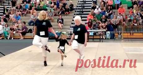 Мама с дочкой и бабушкой танцуют ирландский танец Это семейное трио смотрится мило. Три поколения вместе, держась за руки, отплясывают джигу. Возможно, синхронизация их движений и шагов далека от идеальной.