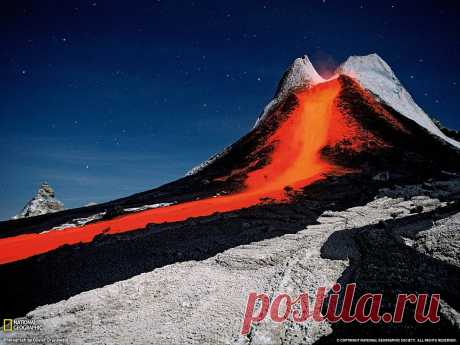 Эта ночная фотография, сделанная с большой выдержкой,  показывает удивительный активный старовулкан Ол Доньо Ленгаи.  Это единственный в мире действующий вулкан,  из которого выходит натрокарбонатная лава,  причем достаточно холодная — около 500-600 градусов по Цельсию.