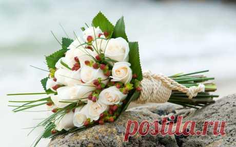 Букет невесты из белых роз перевязанный белой веревкой.