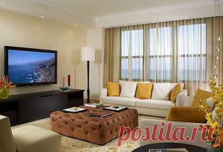 Теплые цвета, со вкусом расставленая мебель и декорации делают эту гостиную идеальным местом для отдыха. Расслабиться на диване во время просмотра ваших любимых фильмов на большом экране телевизора будет очень приятно и комфортно.
