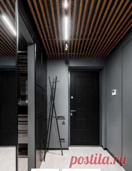 Прихожая с серыми стенами, одностворчатой входной дверью, черной входной дверью, бежевым полом и деревянным потолком - смотрится стильно.