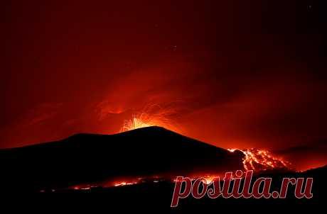 Извержение вулкана Этна ночью 27 июля 2019 года на восточном побережье Сицилии, Италия. Этна — самый высокий и самый активный вулкан в Европе. По данным Национального музея естественной истории (США), в 2018 году высота Этны составляла 3295 м над уровнем моря. Высота вулкана меняется от извержения к извержению — например в 2010 году вулкан был на 21 м ниже, чем в 1981 году.