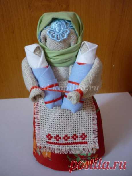 La muñeca tradicional pública por las manos. La Clase maestra