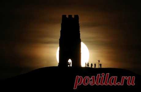 Средневековая башня церкви Св. Михаила на одноименном холме на фоне полной луны. Гластонбери, Великобритания. Холм Св. Михаила издавна связан в народных легендах с именем короля Артура. В 1191 году монахи Гластонберийского аббатства, расположенного неподалеку, объявили, что обнаружили саркофаги с именами Артура и его супруги Гвиневры. В новое же время холм привлекал исследователей паранормальных явлений и оккультистов, заявлявших, что он является порталом в потусторонние миры.