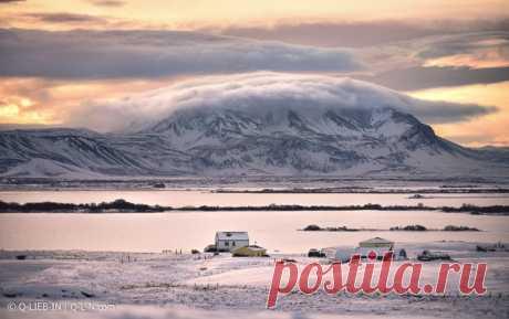 «Домики, тракторы и гора в облачной шапке». Рассвет в национальном парке Миватн, Исландия. Автор снимка – Q-lieb-in: nat-geo.ru/community/user/52515/.