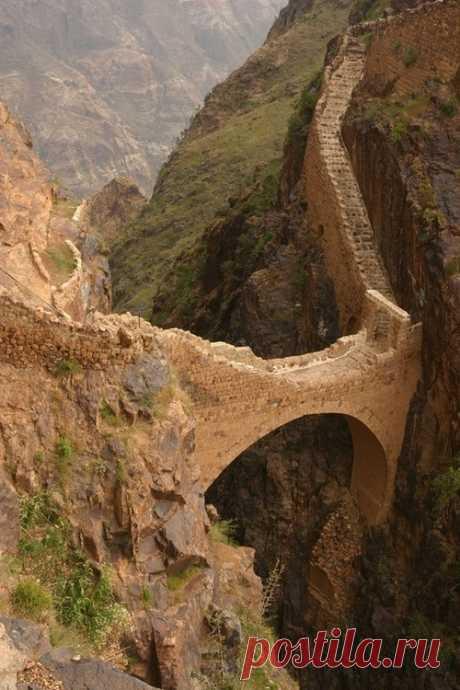 El puente antiguo a través del desfiladero en la cima de las montañas. SHahara, Yemen