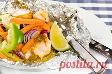 El salmón en el sobre con hortalizas bajo la salsa sazonada.