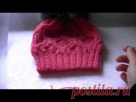 Knitting of a cap a pattern with rhombuses on circular spokes.