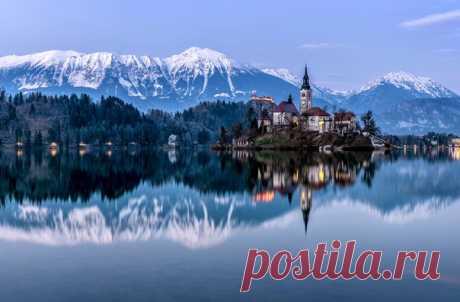 Сергей Кичук, автор фото: «Озеро Блед, в Словении, ледникового происхождения, посередине которого находится маленький островок с Мариинской церковью что на фото. Вокруг озера вид на белоснежные вершины гор Юлианских Альп и все это как в зеркале отражается в прозрачной воде».