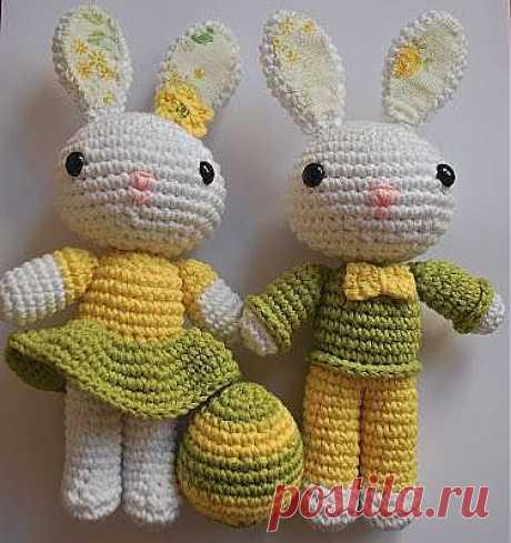 Зайчата девочка и мальчик с пасхальным яйцом.