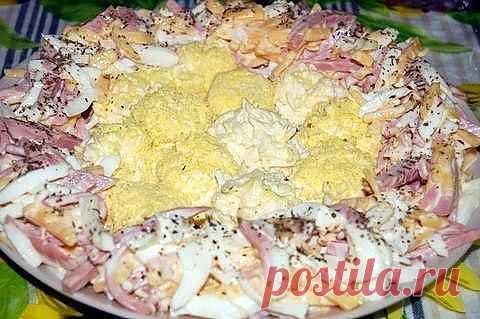 """""""Салат"""" 4 яйца, 200 г ветчины, 150 г твердого сыра, 2 плавленых сырка, 2 зубка чеснока, майонез. Порежьте яичный белок, твердый сыр и ветчину соломкой, смешайте их с майонезом. Плавленый сырок натрите на крупную терку, добавьте давленого чеснока и немного майонеза. Сваляйте из этой массы шарики и обкатайте в тертом желтке (на мелкую терку). Положите яйца на середину большого блюда. Обложите их приготовленной смесью ветчины, сыра с белком и майонезом. Посыпьте сушеной петрушкой или укр"""