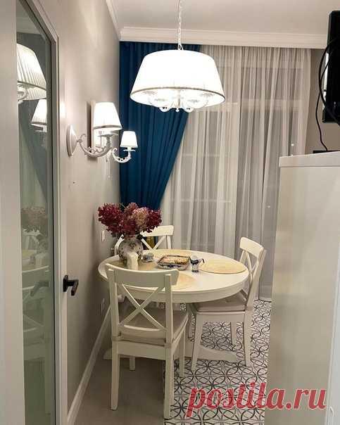 Нежная и прекрасная кухня с верхними фасадами, которые прозрачны. Синия штора разбавляет белый цвет и придает контрастность