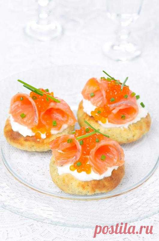 Potato flat cakes with cream cheese, a light-salted salmon and red caviar.