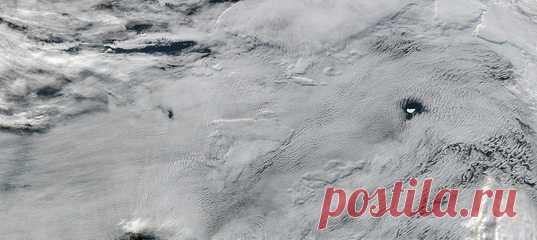 Спутники NASA сделали довольно эффектное изображение южной части Атлантического океана: в центре внимания айсберг в элегантном обрамлении облаков.