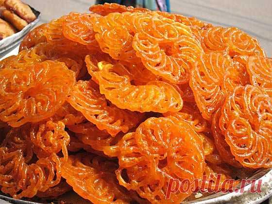 Джалеби. Одна из самых любимых и популярных сладостей в Индии. Это жареные жёлто-оранжевые колечки, пропитанные шафрановым сиропом. Джалеби вкуснее всего сразу же приготовленными, потому что тогда они хрустящие, сочные и ароматные. Когда они остывают, то теряют хрустящесть, а сироп кристаллизируется, но и тогда они очень вкусны. На мой вкус, их лучше всего есть с йогуртом, чтобы смягчить приторную сладость.