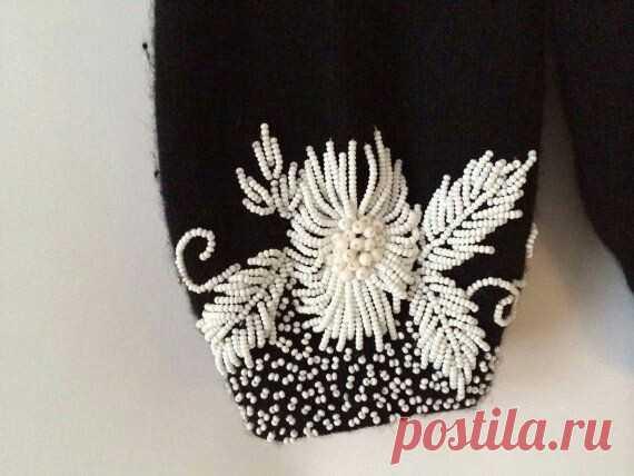 Los abalorios sobre el jersey la ropa A la moda y el diseño del interior por las manos