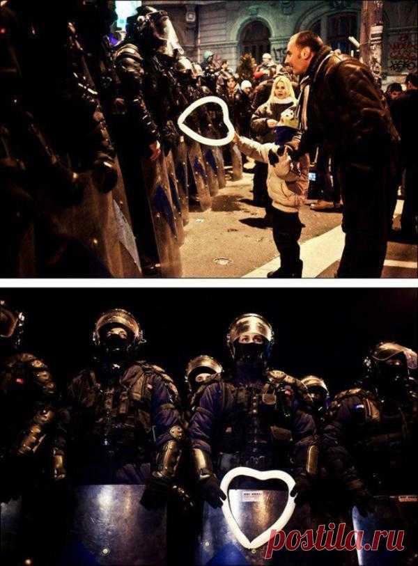 Румынский ребенок вручает воздушный шарик работнику полиции во время протестов в Бухаресте