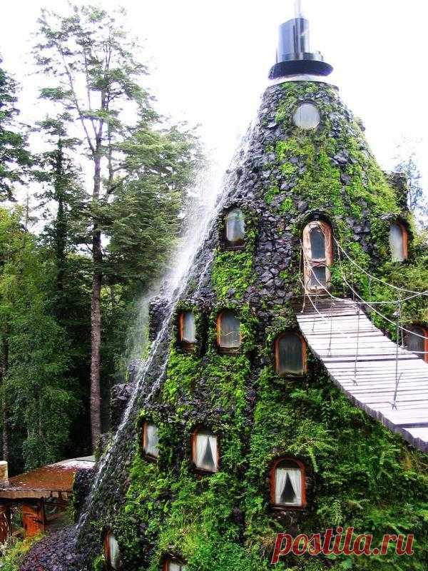 Настоящая экзотика! Похожий на вулкан домик вместо лавы извергает освежающий водопад. Так выглядит отель в Чили. Попасть в отель можно только по подвесному мосту.