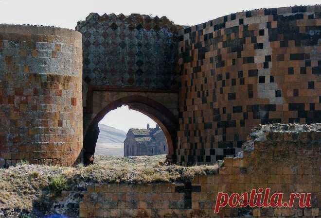 Քաղաքամայր Անիի դարպասներից մեկը. երևում է նաև Անիի Սուրբ Աստվածածին Կաթողիկե եկեղեցին One of the gates of medieval capital Ani. The Cathedral of Ani is seen through the gates.