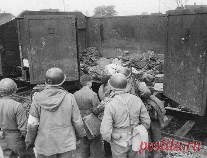 Американские солдаты показывают подросткам из «Гитлерюгенда» тела узников в вагоне, концлагерь Дахау, 1945 год.