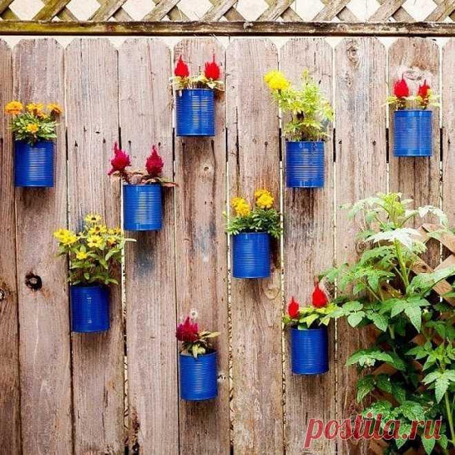Идеи для дачи  Декор стен цветочными горшками (фото)  Цветы — это прекрасная идея для декора. Если на участке есть пустая скучная стена, которую необходимо чем-либо украсить, то подвесные цветы и рамочки с фото будут великолепным вариантом.  1. Для этого необходимо найти пустые жестяные банки или ненужные горшки для цветов, желательно одинакового размера;  2. По бокам проделываются отверстия, в которые нужно пропустить веревку или цепочку. Она будет являться фиксатором для...