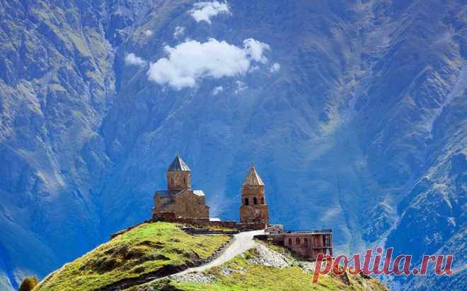 Trinity Church in Gergeti, Georgia. In mountains, at the height of 2170 meters, near the village of Gergeti there is a temple built in the 14th century. From top the picturesque view of the settlement of Stepantsminda and of the village of Gergeti opens.