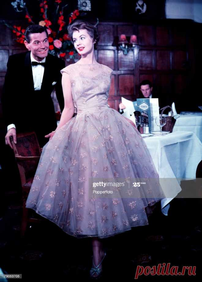 Model is wearing gilt embroidered tulle over satin evening dress, 1957 (Photo by Popperfoto/Getty Images)