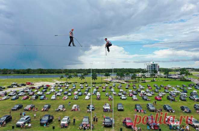 Под куполом неба Акробаты Ник и Блейк Валленда выступают на канате в парке Натана Бендерсона, Сарасота, Флорида, США. Почему все зрители в автомобилях? Рассказываем👇🏻